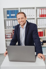 Friendly smiling businessman standing over laptop