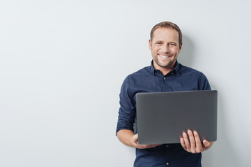 Attractive friendly man holding an open laptop