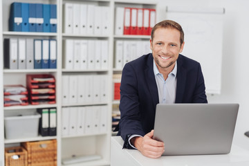 Smiling businessman sitting in office with laptop