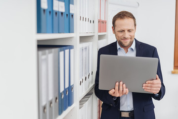 Businessman in the office looking at big tablet