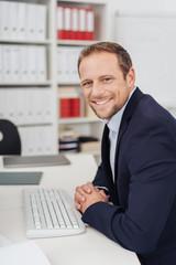 Handsome businessman half-turn portrait in office