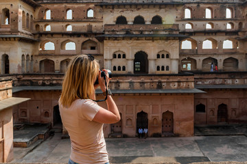 Young woman takes picture of Jahangir Mahal in Orchha, India