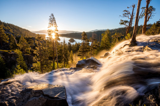 Eagle Falls is illuminated in beautiful golden light at sunrise overlooking Fannette Island and Emerald Bay in Lake Tahoe, California