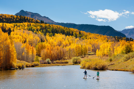 Man and woman on paddleboards in autumn
