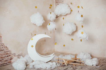 Children's location for a photo shoot. Moon with stars, clouds and airplane. Dreamy decor. Elements of the interior.