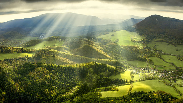 Landscape and nature in the spring. Landscape with dramatic sky and green meadows. The sun rays through the clouds.