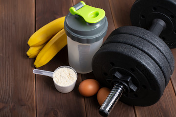 black dumbbell, whey protein, eggs, ban on the wooden floor. View from above.