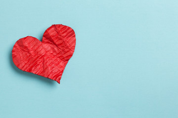 Valentine's Day. Crumpled heart with copy space on cyan background