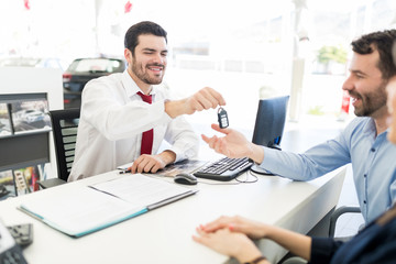 Sales Expert Passing New Car Keys To Customers