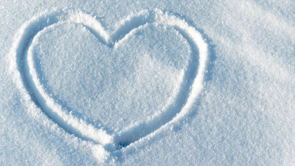 Shape of a heart in the light blue bright snow. Close up leftside view. Valentine's day pattern. Symbol of love