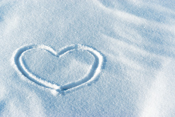 Shape of a heart in the light blue bright snow. Leftside view. Valentine's day pattern. Symbol of love