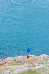 Embankment of Balaclava. Man fisherman catches fish. Blue water. Rocky coast. The texture of the water surface. Black Sea. Yalta. Rest in Crimea. Walk along the beach. Tourism.