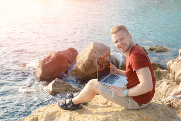 Young guy sitting on coast with laptop. He freelancing. Concept remote work, successful business