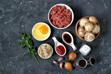 Ingredients for cooking meatloaf: minced meat, mushrooms, egg, white bread, onion, garlic, tomato paste, soy sauce, salt, pepper.