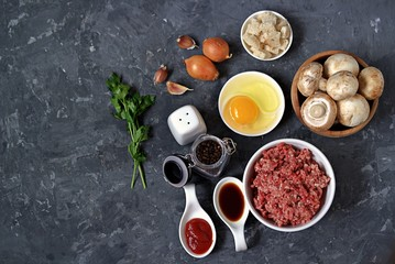 Ingredients for cooking meatloaf: minced meat, eggs, mushrooms, white bread, onion, garlic, tomato paste, soy sauce, salt, pepper. Top view, copy space.