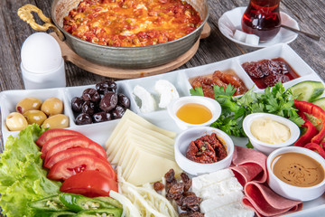 Traditional Turkish breakfast platter on the grey wooden table, top view. Healthy Turkish breakfast in the bright morning; copy space for text.