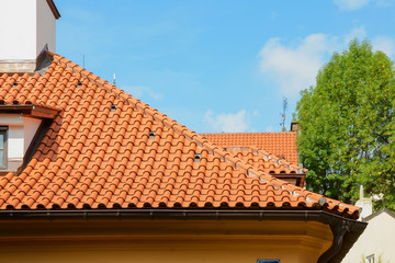 Red ceramic shingles roof with attic windows and chimney against blue sky. Decorative rain gutter.