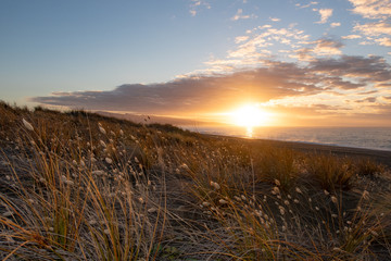 The sun rises over the ocean and Kaitorete Spit warming up the landscape in Canterbury, New Zealand