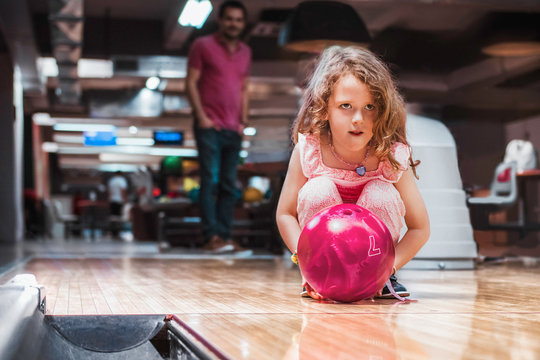 Father and daughter having fun at bowling alley. Proud father watching his little daughter bowling.