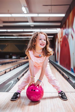 Cute little girl with freckles holding a pink bowling ball, happy with her color choise.