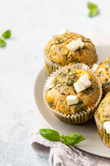 Freshly baked muffins with spinach and feta cheese. Light background. Copy space.