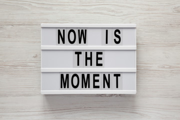 Modern board with text 'Now is the moment' on a white wooden surface, top view. From above, flat lay, overhead.