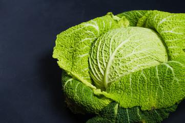 Savoy cabbage. Dark background, side view