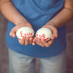 Eggs with the inscription Easter Egg the child holds in her hands in front of him. Toned image. Easter ideas. Space for text. Happy Easter .