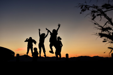 Silhouette of a jumping family at sunset.