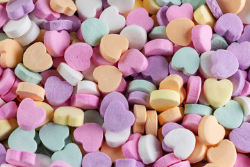 An assortment of conversation hearts taken from top down view.  Pastel colors.