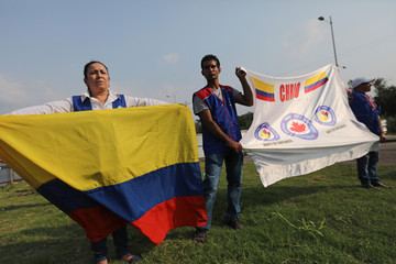 Members of the Canadian Human Rights International Organization of Norte de Santander, protest with a Colombia flag in front of the entrance of the Tienditas cross-border bridge, in Cucuta