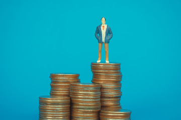 Figure miniature businessman or small people investor and office worker secretary standing on coin stack, for money and financial business success concept.