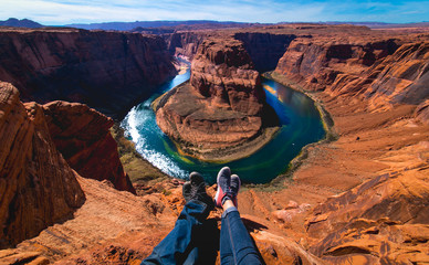 Men and woman sitting together in the edge of the canyon Horseshoe bend in Page, Arizona, United...