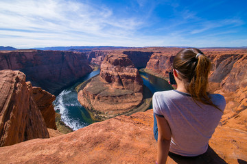 Young woman sitting in the edge of the Horseshoe Bend taking pictures of the landscape with her cellphone. Page, Arizona, United States.