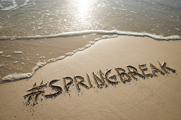 Modern Spring Break message handwritten with a social media hashtag on the smooth sand of an empty beach with an oncoming wave