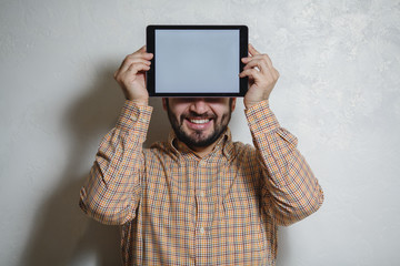 Smiling man holding tablet in hands with white screen. Under the open background.