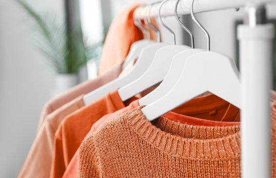 Hangers with orange clothes on rack, closeup