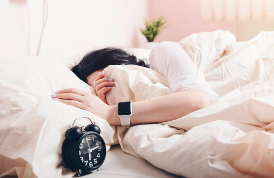 girl on white bed with alarm clock and smart watch on hand