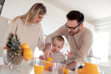 Happy family make orange juice in morning