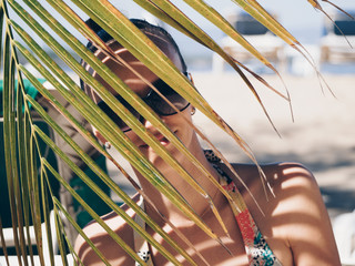 portrait of a young girl in sunglasses on the beach behind a palm branch.