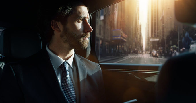 Portrait of young handsome businessman traveling in a modern car with a driver in center of the city by day.