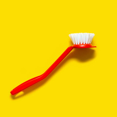 Bright red brush lies on a bright yellow background. In the style of pop art. Top view. Copy space.