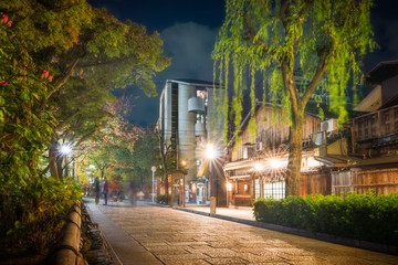 People walking at night in autumn on a traditional street in Gion District, Kyoto, Japan.