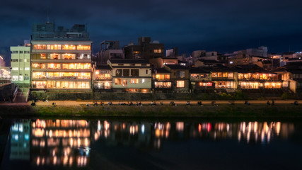 Promenade at night along Kamo River next to Shijoo Bridge in Gion District, Kyoto, Japan.