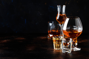 Selection of hard alcoholic drinks in big glasses and small shot glass in assortent: vodka, rum, cognac, tequila, brandy and whiskey. Dark vintage background, selective focus, copy space