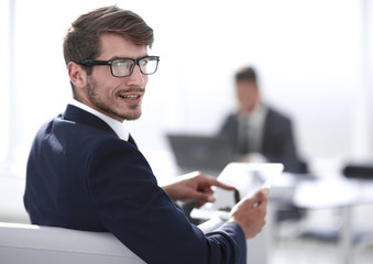 man looks at camera and smiles using tablet