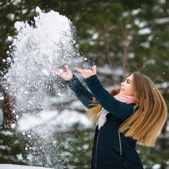 Cute teen girl playing with snow in an amazing winter.