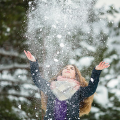 Fun girl playing with snow in an amazing winter.