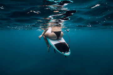 Surfer girl sit at surfboard underwater in blue ocean