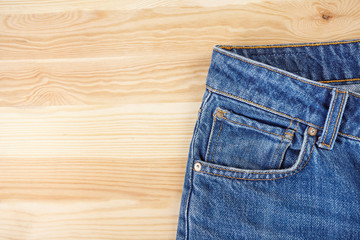 Blue jeans on wooden background.